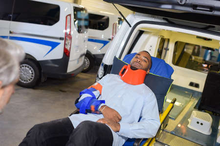 Patient wearing neck brace at rear of ambulance