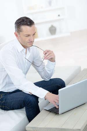man work for laptop on sofa