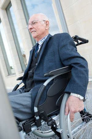 happy old man on wheelchair outdoors
