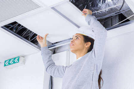 woman holding cables overhead in roofspace