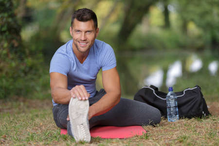 man sat outdoors exercising stretching leg muscles Stock Photo