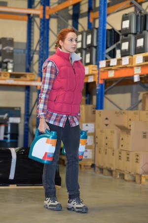 female warehouse worker holding oil bottle