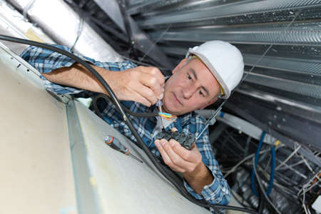 electrician wiring a new building Stock Photo