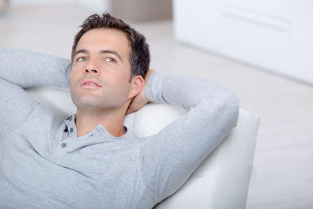 young handsome man relaxing on couch laying and dreaming Stock Photo