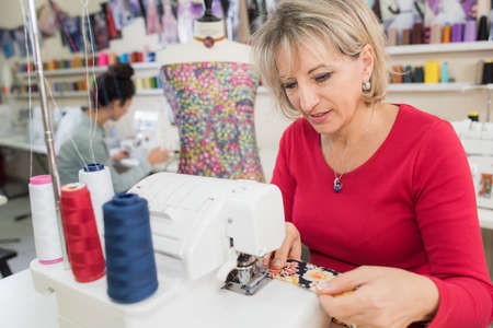middle aged woman using a sewing machine
