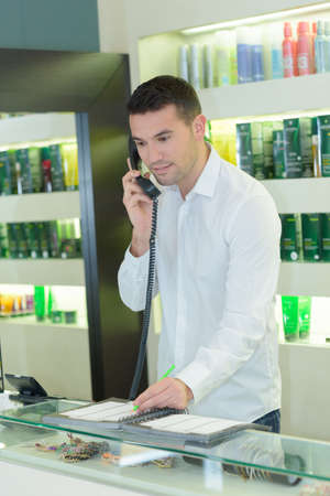 male barber standing by cash register taking booking