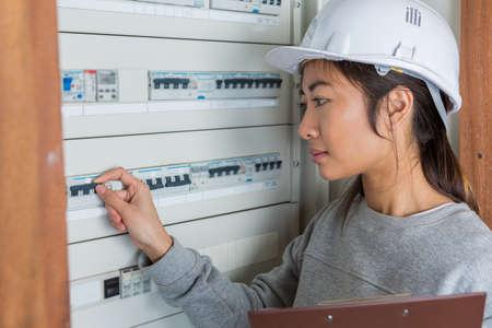 female electrician working on fuse board Stockfoto