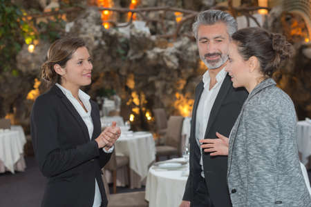 Woman welcoming couple to function Stock Photo