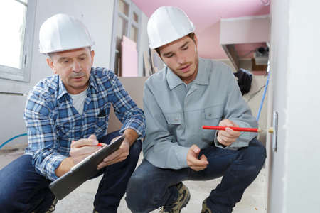two tradesman crouched with clipboard Stock Photo