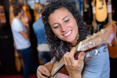 cheerful smiling teenage girl posing with classical guitar in shop