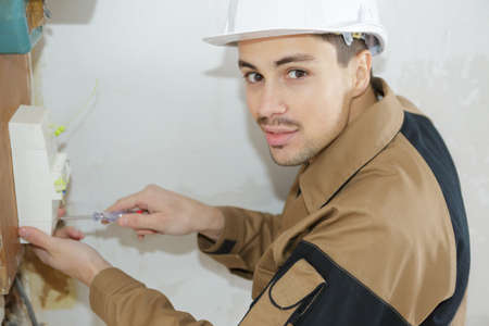 young electrician working on fuse board