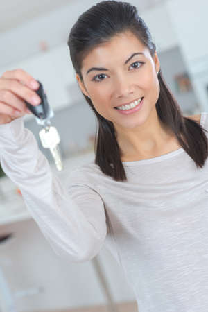 happy female in casual holding appartment keys indoor Stock Photo