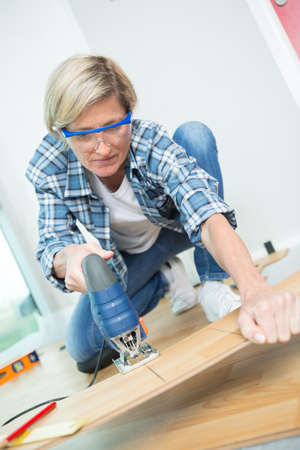 young female carpenter using bandsaw in workshop Stock Photo