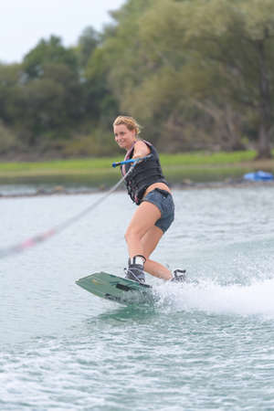 young pretty slim woman riding wakeboard