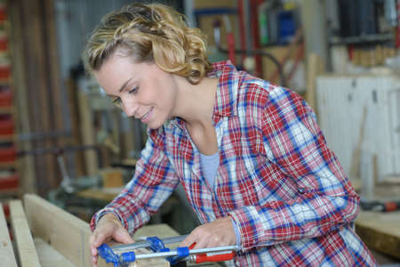 female carpenter using clamp during woodworks Stock Photo