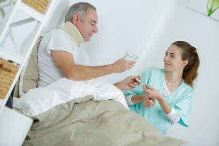 caregiver giving medication to middle-age man on bed