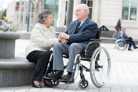 senior on wheelchair with loving wife next to him Stock Photo