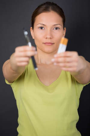woman hand holding an e cigarette and cigarette