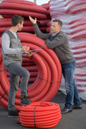 Man stood by industrial sized reels of red conduit