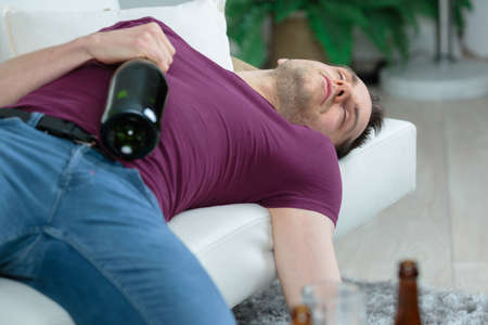 man sleeping holding an alcohol bottle