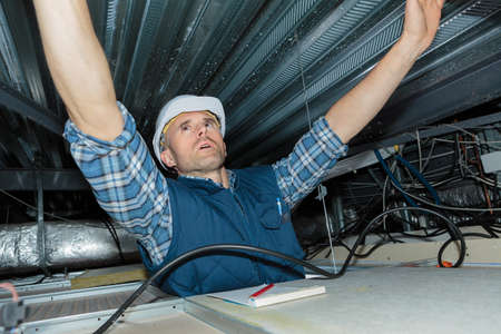 electrician installs wiring in ceiling Banco de Imagens