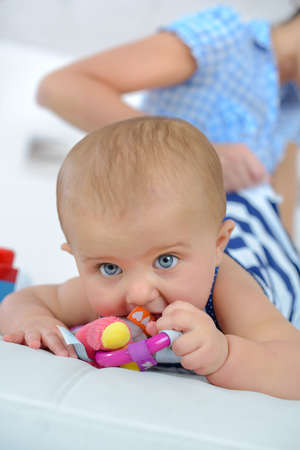 small newborn baby schewing on a plastic rattle