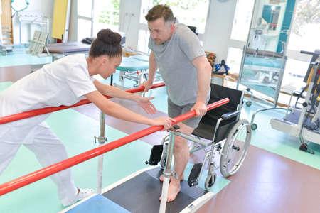 nurse assisting man to walk using walker