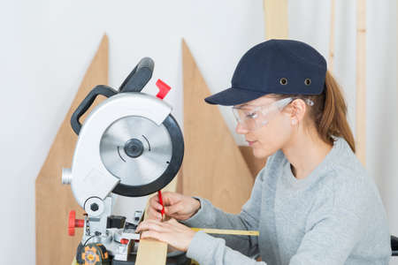 Female carpenter using bench saw Stock Photo