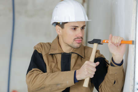 young builder holding chisel and hammer Stock Photo