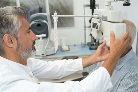 eye specialist examines a patient