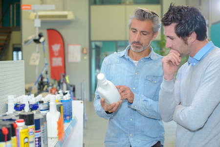 Two men looking at label of mechanical product
