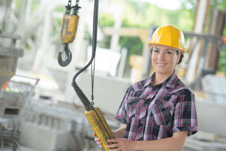 portrait of female worker holding winch controls