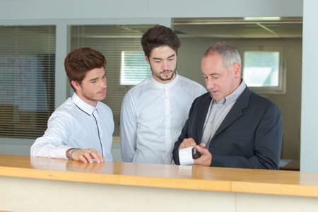 apprentices receptionist at the counter with instructor Archivio Fotografico