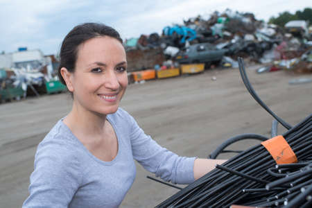 female using a crane with rubbish car scrapyard Stock Photo