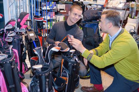 Men looking at golfing equipment in store