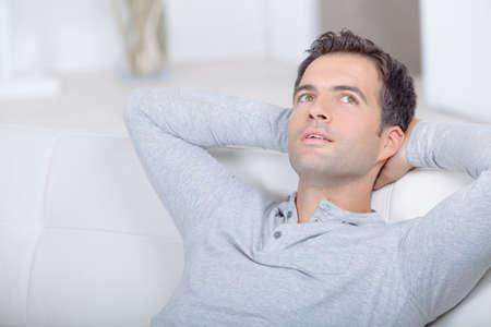 man on sofa daydreaming Stock Photo