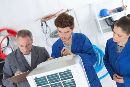 electrician repairman and apprentices fixing air conditioning