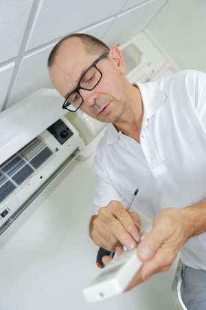 man adjusting thermostat of an air conditioning system