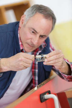 worker holding a door lock profile cylinder in his hands