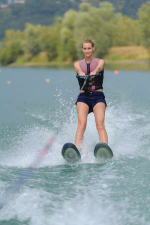 young pretty slim woman riding wakeboard in a lake