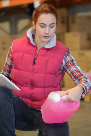 female worker in warehouse checking stock with tablet