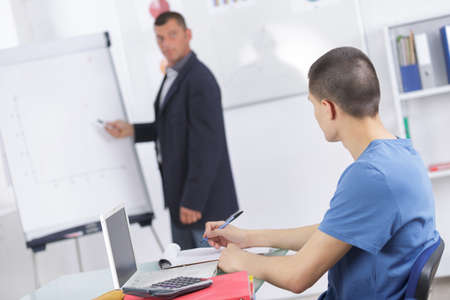teacher with adult students in classroom