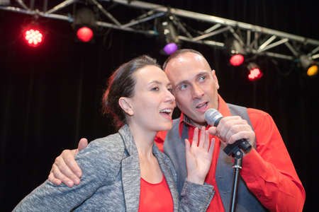 Couple singing on stage Stock Photo