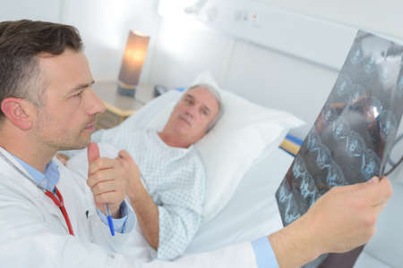mature doctor examinating patients xray at the hospital Reklamní fotografie