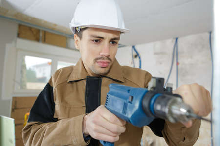 man with drill or screwdriver and construction