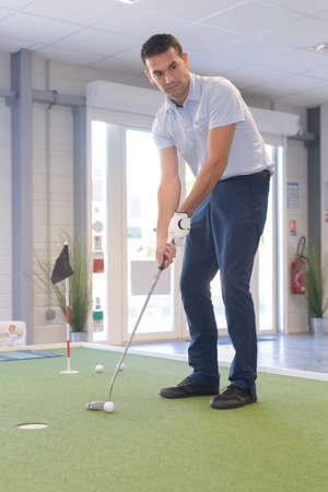 man playing indoor golf Foto de archivo