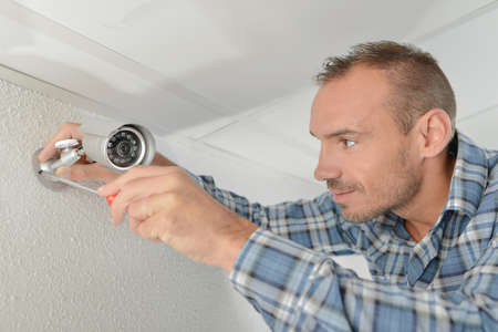 technician adjusting cctv camera on wall Stock Photo
