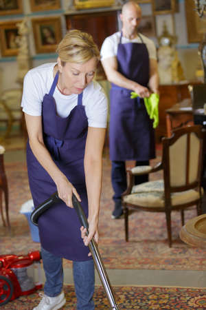 team hoovering carpet with vacuum cleaner at home 免版税图像
