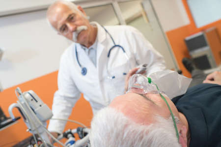 doctor examining the patient wearing breathing mask