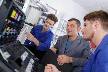 apprentices fixing photo copier Stock Photo